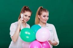 2 девушки с мобильным телефоном и воздушными шарами Стоковое фото RF