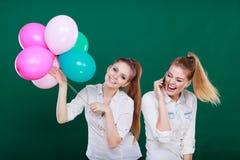 2 девушки с мобильным телефоном и воздушными шарами Стоковые Изображения RF