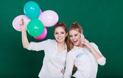 2 девушки с мобильным телефоном и воздушными шарами Стоковые Фотографии RF