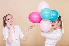 2 девушки с мобильным телефоном и воздушными шарами Стоковые Изображения
