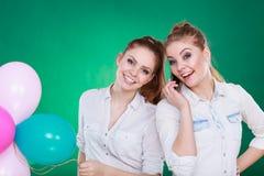 2 девушки с мобильным телефоном и воздушными шарами Стоковые Фото