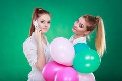 2 девушки с мобильным телефоном и воздушными шарами Стоковое Изображение