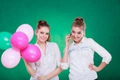2 девушки с мобильным телефоном и воздушными шарами Стоковое Фото