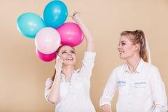 2 девушки с мобильным телефоном и воздушными шарами Стоковое Изображение RF