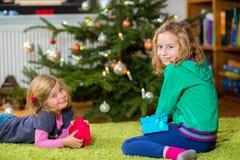2 девушки с настоящими моментами перед рождественской елкой Стоковые Фотографии RF