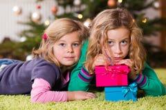 2 девушки с настоящими моментами перед рождественской елкой Стоковая Фотография