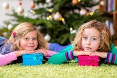 2 девушки с настоящими моментами перед рождественской елкой Стоковое Изображение