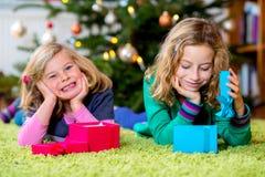 2 девушки с настоящими моментами перед рождественской елкой Стоковые Фото