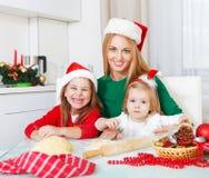 2 девушки с печеньями рождества выпечки матери в кухне Стоковые Фото