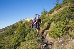 2 девушки с прогулкой рюкзаков вдоль следа Стоковые Изображения RF