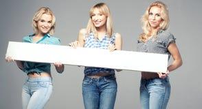 3 девушки с пустой доской Стоковое фото RF
