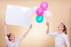 2 девушки с пустыми доской и воздушными шарами Стоковая Фотография