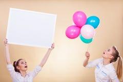 2 девушки с пустыми доской и воздушными шарами Стоковое Изображение