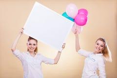 2 девушки с пустыми доской и воздушными шарами Стоковые Изображения