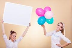 2 девушки с пустыми доской и воздушными шарами Стоковое фото RF