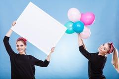 2 девушки с пустыми доской и воздушными шарами Стоковые Фотографии RF