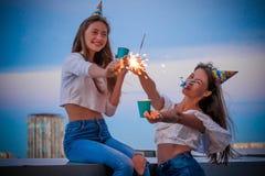 2 девушки с светами Бенгалии и бумажными стеклами празднуют их день рождения стоковое изображение rf