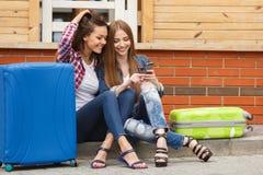 2 девушки с сумками читая текстовое сообщение пока сидящ на станции Стоковые Изображения