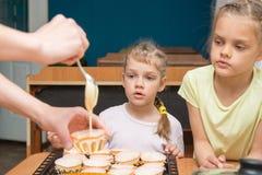 2 девушки с удивленный выглядеть как мама льют бэттер в прессформы для пирожных Стоковые Фото