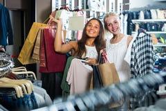 2 девушки с хозяйственными сумками в магазине Стоковые Изображения RF