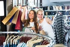 2 девушки с хозяйственными сумками в магазине Стоковые Изображения