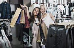 2 девушки с хозяйственными сумками в магазине Стоковое Фото