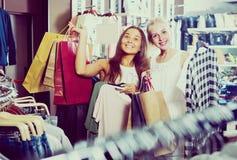 2 девушки с хозяйственными сумками в магазине Стоковые Фото