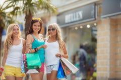 3 девушки с хозяйственными сумками и идут ходить по магазинам Стоковое Изображение