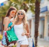 3 девушки с хозяйственными сумками и идут ходить по магазинам Стоковые Изображения RF