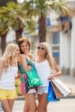 3 девушки с хозяйственными сумками и идут ходить по магазинам Стоковые Фото