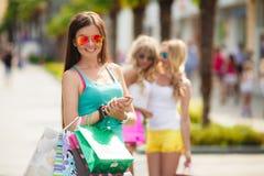 3 девушки с хозяйственными сумками и идут ходить по магазинам Стоковая Фотография