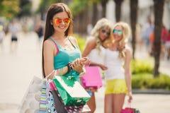 3 девушки с хозяйственными сумками и идут ходить по магазинам Стоковое фото RF