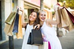 2 девушки с хозяйственными сумками outdoors Стоковое Фото
