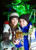 2 девушки с шампанским около рождественской елки Стоковое Изображение
