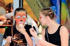 2 девушки с narisoval маской тигра на его стороне есть мороженое Стоковое Изображение RF