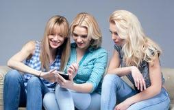 3 девушки с smartphone Стоковые Фотографии RF