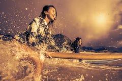 2 девушки с Surfboard в воде брызгают Стоковое фото RF
