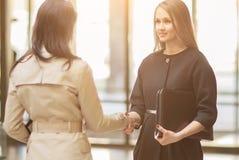 2 девушки тряся руки в современном офисе, усмехаясь и смотря один другого на солнечный день Стоковые Изображения