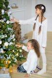 2 девушки украшают рождественскую елку Стоковые Фотографии RF