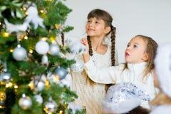 2 девушки украшают рождественскую елку Стоковые Изображения RF