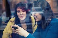 2 девушки усмехаясь и используя умный телефон в кафе Стоковые Изображения