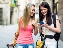 2 девушки усмехаясь на каникулах с багажом Стоковое Изображение