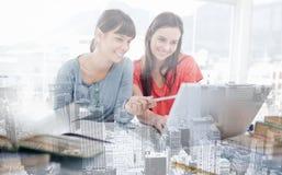 2 девушки усмехаясь по мере того как они используют компьтер-книжка как одна девушка указывают на что-то Стоковое фото RF
