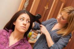 2 девушки утюжа волосы Стоковые Фотографии RF