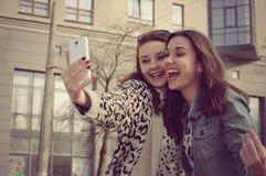 2 девушки фотографируя и смеяться над Стоковые Фотографии RF