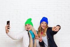 2 девушки фотографируя selfie, друзья женщин представляя умную камеру фото телефона Стоковые Изображения RF