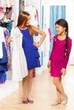 2 девушки ходят по магазинам и одна спрашивает другую о платье Стоковое Изображение RF