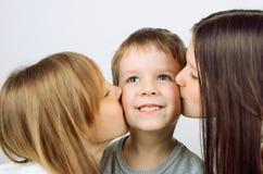2 девушки целуя маленького жизнерадостного мальчика Стоковое Изображение