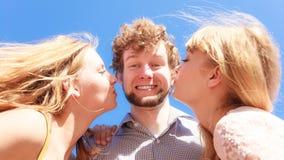 2 девушки целуя одного мальчика имея потеху внешнюю Стоковая Фотография RF