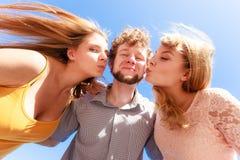 2 девушки целуя одного мальчика имея потеху внешнюю Стоковое фото RF